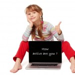 Little girl sitting on floor showing laptop screen